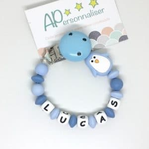 https:www.apersonnaliser.frwp contentuploads2020accroche tetine a personnaliser forme pingouin bleu silicone prenom
